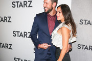 Pablo Schreiber and Melissa Barrera are seen attending the 2019 Winter TCA Tour - STARZ 'American Gods' Premiere at 71Above in Los Angeles, California.