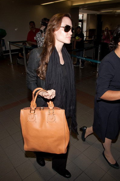 Angelina Jolie ****NO GERMANY / SWITZERLAND****.Angelina prepares to depart LAX (Los Angeles International Airport) carrying a large handbag.