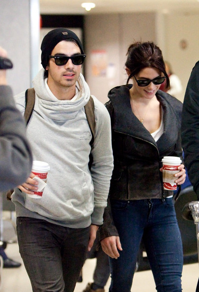 Ashley Greene and Joe Jonas arrive at LAX (Los Angeles International Airport) carrying matching Starbucks cups and a puppy.