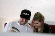 Avril Lavigne and Brody Jenner arrive at Nice Airport where they browse a convenience store before their departure. The couple then cuddles on a bench and peruse a magazine called 'Super Yacht World' while they wait.