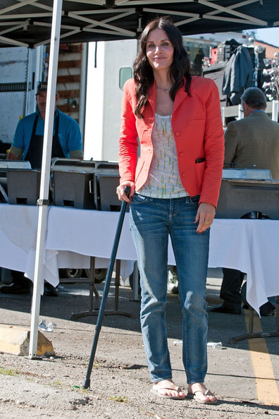 "Courteney Cox walks to and from set using a cane.  It seems as if she has difficulty walking and her friendly ""Cougar Town"" crewmembers assist her to her trailer in between takes.  Though she may be in pain, she still smiles for the camera."