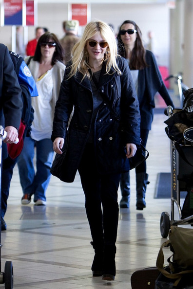Dakota Fanning dresses in dark attire as she prepares to depart LAX (Los Angeles International Airport).