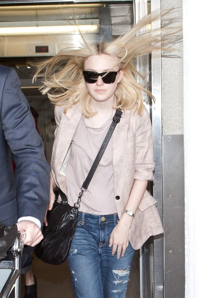 Dakota Fanning's hair flies in the wind as she arrives at LAX (Los Angeles International Airport).