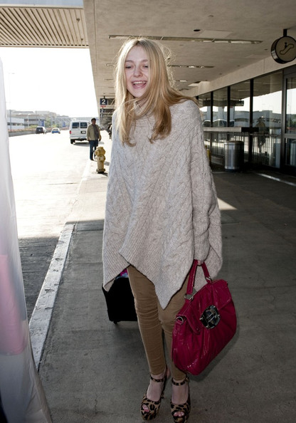 Dakota Fanning lands at LAX covered in a poncho.