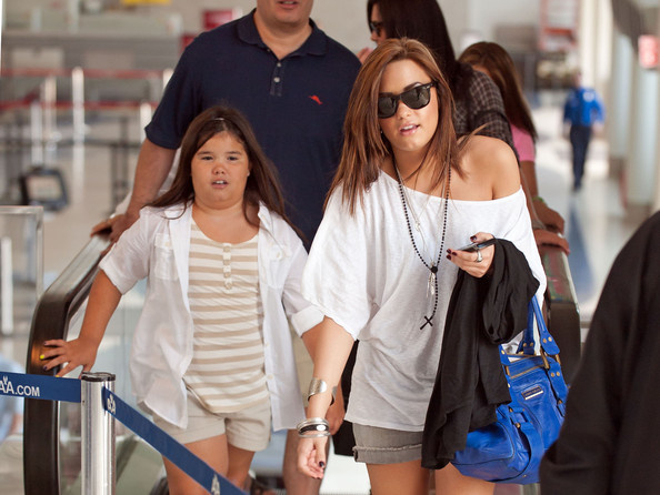 Demi Lovato shows of her new blonder hairstyle and sticks her tongue out at little sister Madison De La Garza as the family departs Los Angeles International Airport (LAX).