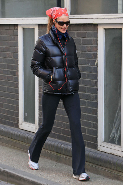 Elle Macpherson pulls her hair back with a red bandana that matches her red headphones while on the school run.