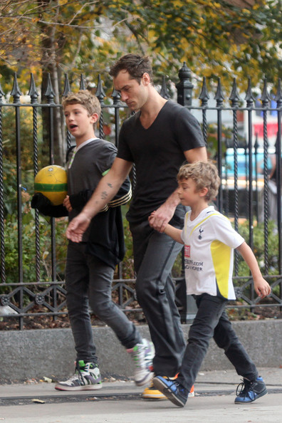 Jude Law plays a game of soccer with his two sons, Rafferty (b.