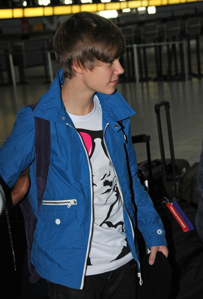 Justin Bieber Justin Bieber avoids the cameras as he makes his way through JFK airport.