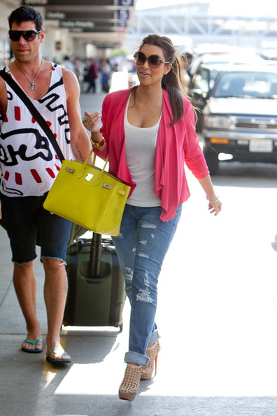 Kim Kardashian prepares to depart LAX (Los Angeles International Airport) wearing bright colors.