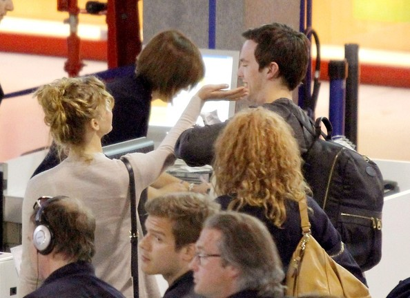 Jennifer Lawrence and Nicholas Hoult look every bit the flirtatious young couple as she takes a playful swipe at him while preparing to depart out of Nice Cote d'Azur Airport.