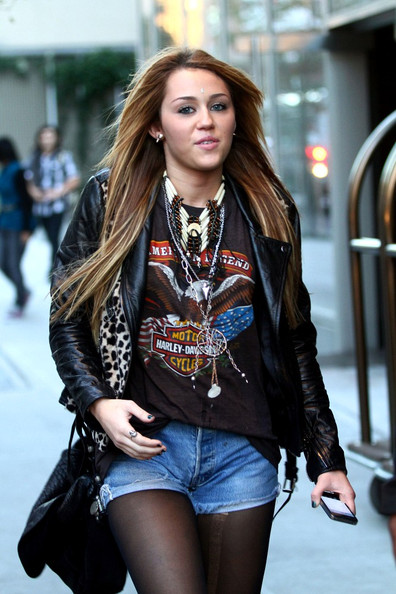 Miley Cyrus Miley Cyrus looks like a rocker chick as she leaves her hotel acting a bit shy for the camera.