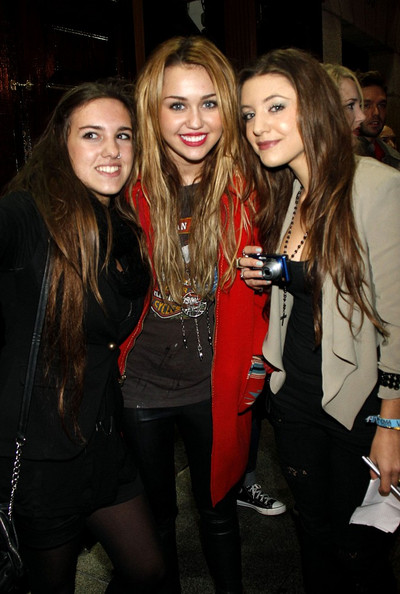 Miley Cyrus Miley Cyrus stands out in a bright red coat while out partying with friends.