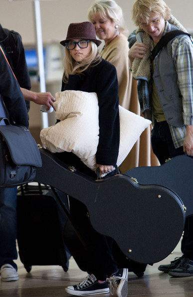 Emily Osment 'Hannah Montana' star Emily Osment strums her guitar as she prepares to depart Los Angeles International Airport (LAX) for a tour with her band 'Push Play.'.