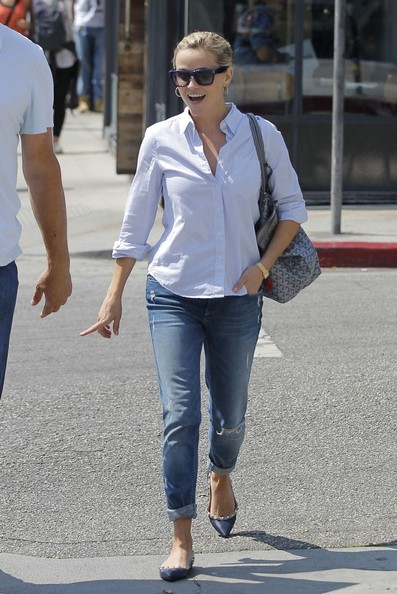 Reese Witherspoon looks tiny next to her much larger lunch companion as they leave a restaurant in Venice.