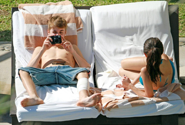 Selena Gomez Justin Bieber and Selena Gomez take time out of their busy tour schedules to relax on a lounge chair by the pool while on holiday. The young lovebirds get flirty with one another as Selena reaches across Justin for her phone, and then strikes a pose as he takes her photograph.