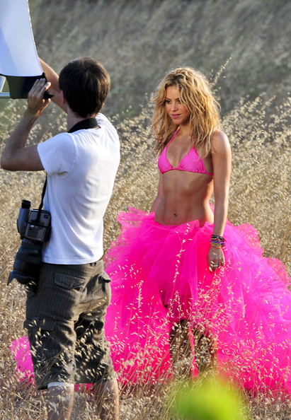 Shakira Shakira stands out in hot pink for a photo shoot in a field. The singer shows off her flexibility by stretching for some poses.