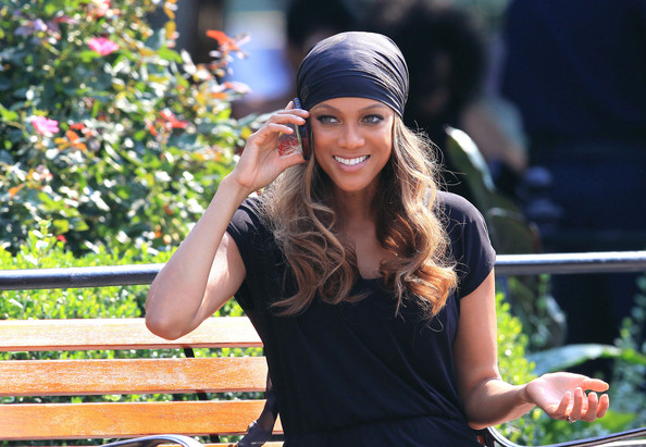 Tyra Banks chats away on her cell phone whilst on the set of a video shoot in Union Square.