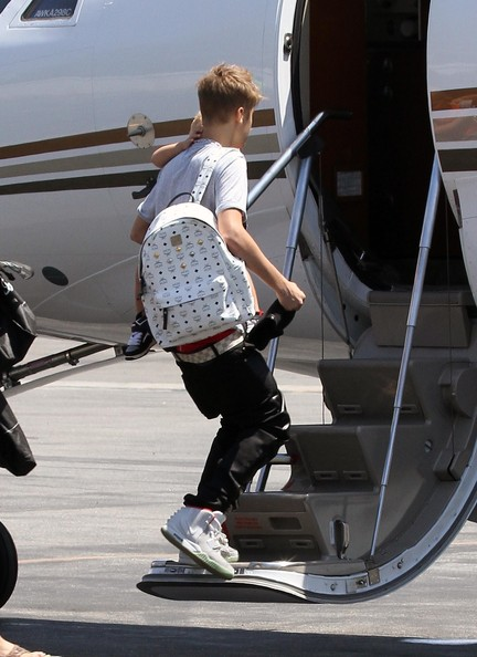 Justin Bieber Singer Justin Bieber caught a flight out of town on a private jet in Van Nuys, California on August 1, 2012. Justin was carrying his little brother Jaxon Bieber as he boarded the plain with his family and entourage.