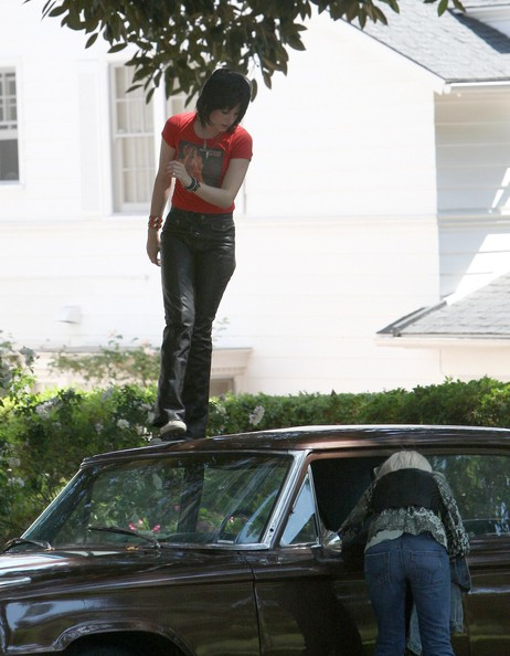 Actresses Kristen Stewart and Dakota Fanning on the set of 'The Runaways' in Los Angeles. Dakota fell and had a big laugh and the girls were seen jumping on a car and kicking over a trash can.