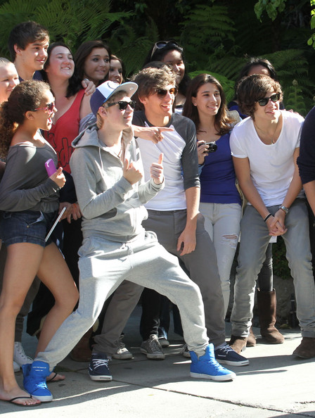 British boy band One Direction poses with some lucky female fans outside their hotel on April 4, 2012 in Westwood, CA.