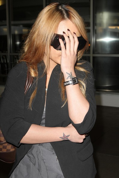 3 star tattoos on wrist. Reality star Tila Tequila trying to hide her face as she arrives on a flight
