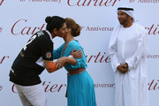 HRH Princess Haya Bint Al Hussein kisses HH Sheikha Maitha during the presentations as Ali Al Bawardi looks on during the final day of the Cartier International Dubai Polo Challenge 10th edition at Desert Palm Hotel on February 21, 2015 in Dubai, United Arab Emirates. The event takes place under the patronage of HRH Princess Haya Bint Al Hussein, Wife of HH Sheikh Mohammed Bin Rashid Al Maktoum, Vice-President and Prime Minister of the UAE and Ruler of Dubai.  The Cartier International Dubai Polo Challenge is one of the most prestigious happenings in Dubai's sporting and social calendar. On this occasion Cartier launched their latest watch creation Cle De Cartier.