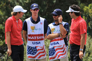 Webb Simpson of the U.S. Team (L) chats with team mate Bubba Watson and his caddie Ted Scott, along with Simpson's caddie Paul Tesori, on the 10th hole during the Day Two Four-Ball Matches of the 2011 Presidents Cup at Royal Melbourne Golf Course on November 18, 2011 in Melbourne, Australia.