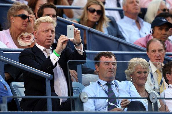 Boris Becker takes a photograph with his phone next to AELTC Chairman Philip Brook and his wife Gill Brook watches the women's singles final match between Victoria Azarenka of Belarus and Serena Williams of the United States of America on Day Fourteen of the 2013 US Open at the USTA Billie Jean King National Tennis Center on September 8, 2013 in the Flushing neighborhood of the Queens borough of New York City.