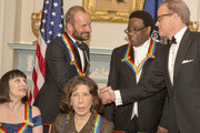 Singer-songwriter Sting, top left, one of the five recipients of the 2014 Kennedy Center Honors, shakes hands with Michael Stevens, top right, writer and producer of the annual Kennedy Center Honors as they wait to pose for a group photo following a dinner hosted by United States Secretary of State John F. Kerry at the U.S. Department of State on December 6, 2014 in Washington, D.C.