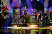 Singer Chris Martin (C) and musicians (L-R) Jonny Buckland, Will Champion and Guy Berryman of Coldplay perform onstage during the 2015 American Music Awards at Microsoft Theater on November 22, 2015 in Los Angeles, California.