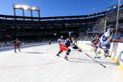 Kyle Okposo #21 of the Buffalo Sabres and Mika Zibanejad #93 of the New York Rangers vie for the puck along the boards during the first period of the 2018 Bridgestone NHL Winter Classic between the New York Rangers and the Buffalo Sabres at Citi Field on January 1, 2018 in the Flushing neighborhood of the Queens borough of New York City.