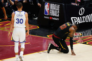 LeBron James #23 of the Cleveland Cavaliers kneels after a play as Stephen Curry #30 of the Golden State Warriors looks on in the first half during Game Four of the 2018 NBA Finals at Quicken Loans Arena on June 8, 2018 in Cleveland, Ohio. NOTE TO USER: User expressly acknowledges and agrees that, by downloading and or using this photograph, User is consenting to the terms and conditions of the Getty Images License Agreement.