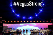 """#VegasStrong"" is displayed on a video screen while Jason Aldean (center R) and Bobby Bones (center L) honor first responders onstage during the 2018 iHeartRadio Music Festival at T-Mobile Arena on September 21, 2018 in Las Vegas, Nevada."