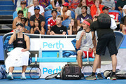 Alexander Zverev of Germany receives medical treatment as Angelique Kerber looks on while playing the mixed doubles match against David Ferrer and Garbine Muguruza of Spain during day two of the 2019 Hopman Cup at RAC Arena on December 30, 2018 in Perth, Australia.
