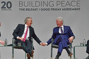Former US President Bill Clinton holds (R) hands with former British Prime Minister Tony Blair as they attend an event to mark the 20th anniversary of the Good Friday Agreement at Queens university on April 10, 2018 in Belfast, Northern Ireland. Northern Ireland's present devolved system of government is based on this agreement and was a major part of the 1990's peace process.