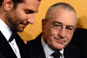 "Actors Bradley Cooper (L) and Robert De Niro, winners of the Outstanding Performance by a Cast in a Motion Picture award for ""American Hustle,"" pose in the press room during the 20th Annual Screen Actors Guild Awards at The Shrine Auditorium on January 18, 2014 in Los Angeles, California."