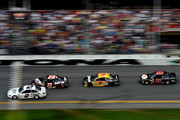 Brad Keselowski, driver of the #2 Miller Lite Ford, leads Alex Bowman, driver of the #23 Dr. Pepper Toyota, Michael Annett, driver of the #7 Pilot/Flying J Travel Centers Chevrolet, and Josh Wise, driver of the #98 Curb Records Ford, during the NASCAR Sprint Cup Series Daytona 500 at Daytona International Speedway on February 23, 2014 in Daytona Beach, Florida.