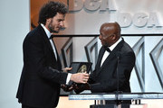 """Director Garth Davis accepts the First-Time Feature Film Plaque for """"Lion"""" onstage from director John Singleton during the 69th Annual Directors Guild of America Awards at The Beverly Hilton Hotel on February 4, 2017 in Beverly Hills, California."""