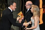 (L-R) Presenter Tom Hanks greets Production Designer Dante Ferretti and Set Decorator Francesca Lo Schiavo, winners of the Best Art Direction Award for 'Hugo,' onstage during the 84th Annual Academy Awards held at the Hollywood & Highland Center on February 26, 2012 in Hollywood, California.