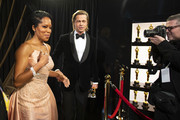 In this handout photo provided by A.M.P.A.S. Regina King and Best Actor in a Supporting Role winner Brad Pitt look on backstage during the 92nd Annual Academy Awards at the Dolby Theatre on February 09, 2020 in Hollywood, California.