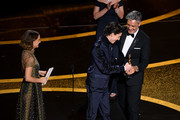 (L-R) Natalie Portman and Timothée Chalamet present the Writing - Adapted Screenplay - award for 'Jojo Rabbit' to   Taika Waititi onstage during the 92nd Annual Academy Awards at Dolby Theatre on February 09, 2020 in Hollywood, California.