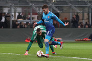 Aaron Ramsey of Arsenal rounds AC Milan goalkeeper Gianluigi Donnarumma to score during the UEFA Europa League Round of 16 match between AC Milan and Arsenal at the San Siro on March 8, 2018 in Milan, Italy.