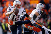 Tom Brady #12 of the New England Patriots tries to evade a tackle by  Von Miller #58 of the Denver Broncos in the first half in the AFC Championship game at Sports Authority Field at Mile High on January 24, 2016 in Denver, Colorado.