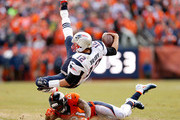 Tom Brady #12 of the New England Patriots is tackled by  Aqib Talib #21 of the Denver Broncos after an 11 yard scramble in the second quarter in the AFC Championship game at Sports Authority Field at Mile High on January 24, 2016 in Denver, Colorado.
