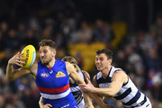 Marcus Bontempelli of the Bulldogs breaks free of a tackle by Mark Blicavs and Jack Henry of the Cats during the round 15 AFL match between the Western Bulldogs and the Geelong Cats at Etihad Stadium on June 29, 2018 in Melbourne, Australia.