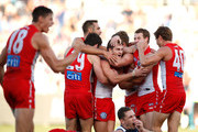 Swans players (L-R) Josh Kennedy, George Hewett, Tom Papley, Luke Parker, Harry Cunningham and Nick Smith celebrate on the final siren during the 2018 AFL round six match between the Geelong Cats and the Sydney Swans at GMHBA Stadium on April 28, 2018 in Geelong, Australia.