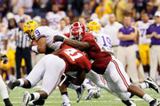 Jordan Jefferson #9 of the Louisiana State University Tigers gets tackled by Courtney Upshaw #41 and Quinton Dial #90 of the Alabama Crimson Tide during the 2012 Allstate BCS National Championship Game at Mercedes-Benz Superdome on January 9, 2012 in New Orleans, Louisiana.