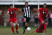 Dominic Cope (2L) of Alresford Town is challenged by Chris Mason (L) of Winchester City during the FA Cup Extra Preliminary Round match between Alresford Town and Winchester City at Alrebury Park on August 16, 2013 in New Alresford, England.