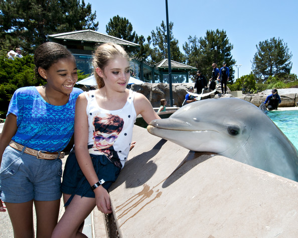 "In this handout image provided by SeaWorld San Diego, ""The Hunger Games"" co-stars Amandla Stenberg and Willow Shields made a new friend in Cocoa, a bottlenose dolphin, at SeaWorld San Diego's Dolphin Point on July 15, 2012 in San Diego, California.  The two young actresses were in San Diego participating in the 43rd annual Comic-Con when they made their visit to the marine-life park.  Along with dolphins, Shields and Stenberg also met penguins, seals and sea lions."