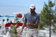 NFL athlete Aaron Rodgers of the Green Bay Packers catches a football thrown to him from fans on the beach during round one of the American Century Championship at Edgewood Tahoe South golf course on July 10, 2020 in Lake Tahoe, Nevada.